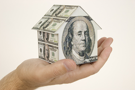 A hand holding a house made of money